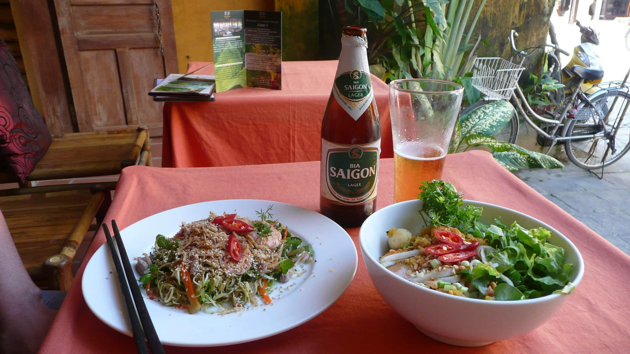 A photo of a lunch of banana flower salad and a bowl of beef pho accompanied by a cold Saigon beer in Hoi An Vietnam